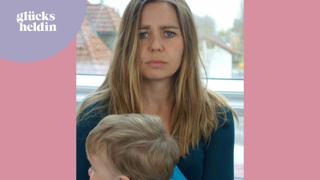 Auf dem Bild sieht man eine Mutter mit Baby auf dem Arm. Sie sieht erschöpft aus und traurig. Eine Träne rinnt ihr übers Gesicht.