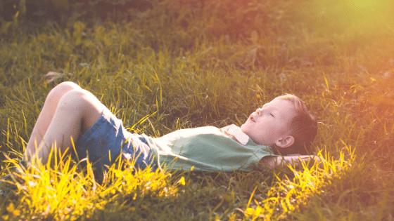 kind liegt auf wiese entspann hat zuviel stress